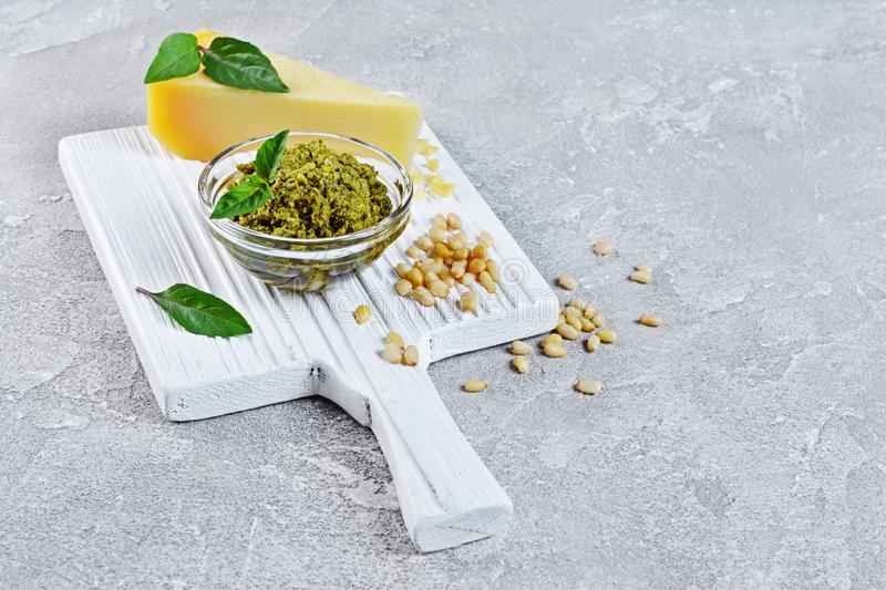 Traditional italian green sauce pesto in glass bowl with parmesan cheese, pine nuts and basil leaves on wooden board royalty free stock photos