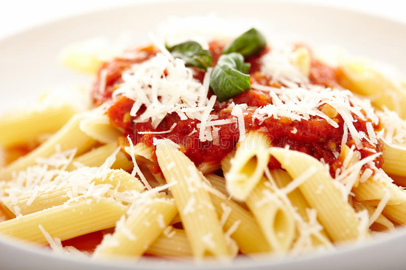 Traditional italian pasta with tomato and pepperoni sauce decorated with basil stock images