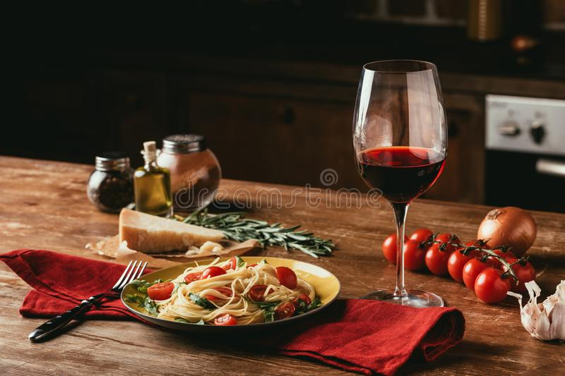 Traditional Italian pasta with tomatoes and arugula in plate and glass of stock photography
