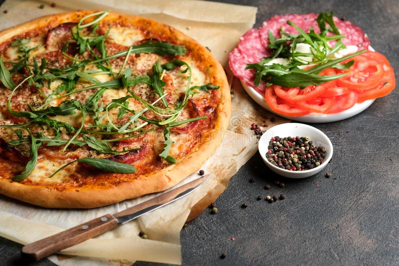 Traditional Italian pizza with ingredients. On a dark background. Copy space royalty free stock photography
