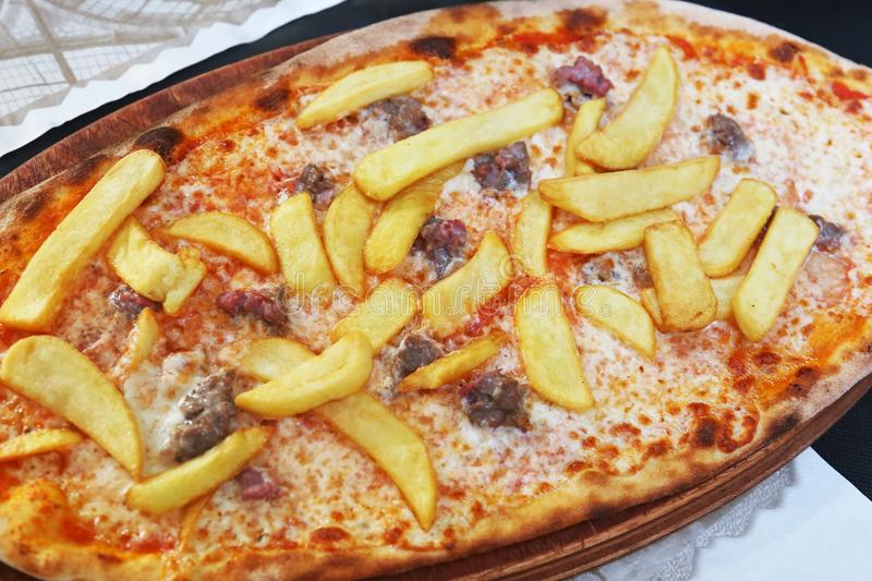 Traditional italian pizza with potato fries, sausages, cheese and tomato sauce royalty free stock photography