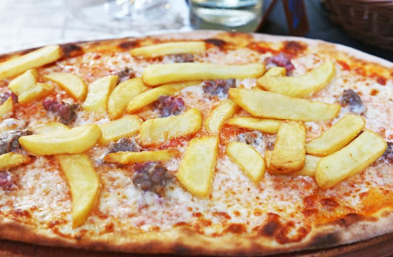 traditional italian pizza with potato fries, sausages, cheese and tomato sauce stock photo