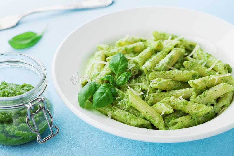 Traditional italian plate of pasta with pesto sauce decorated basil leaves and cheese. stock photography
