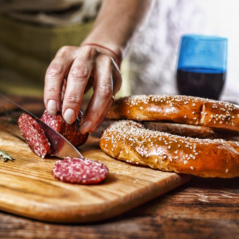 Traditional Italian red wine, salami, rosemary, bread. Close up of a person`s hand cut salami on a kitchen board. royalty free stock photos