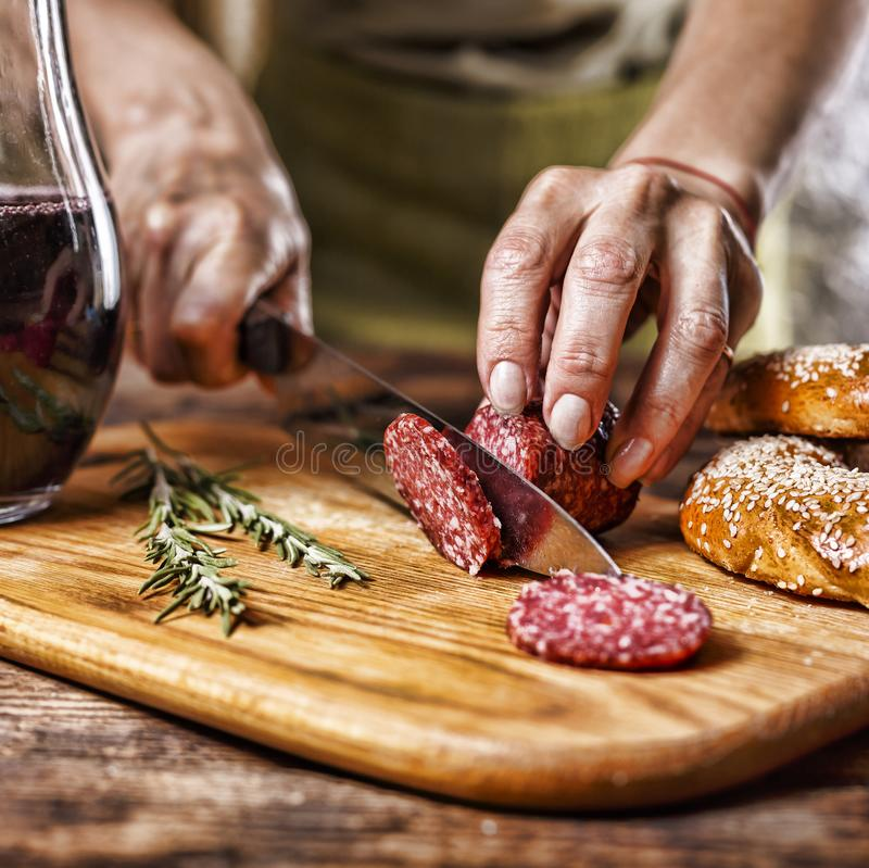 Traditional Italian red wine, salami, rosemary, bread. Close up of a person`s hand cut salami on a kitchen board. stock image