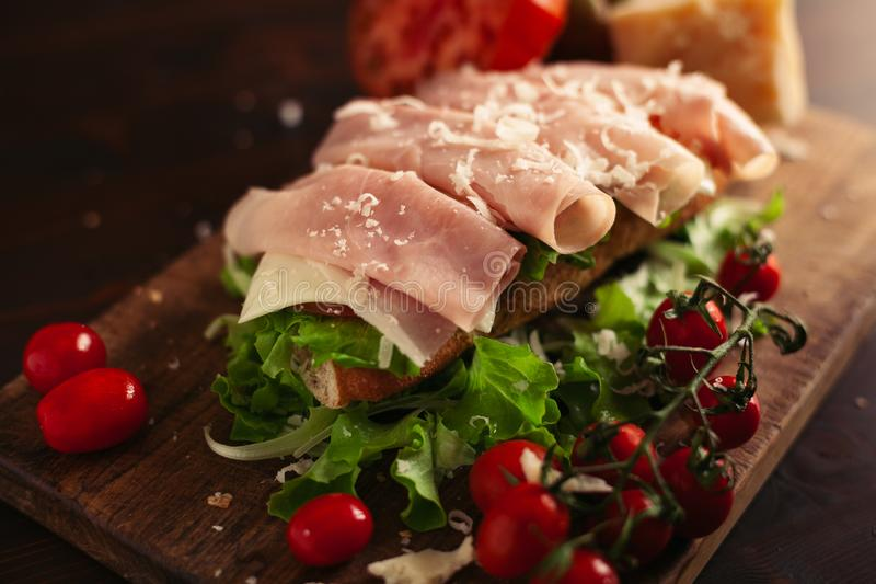 Traditional italian sandwich with cheese, ham, salad, tomatoes and parmesan on wooden background, selective focus royalty free stock photo