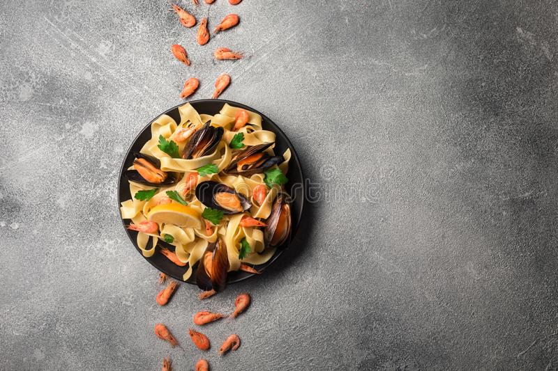 Traditional italian seafood pasta with clams Spaghetti alle Vongole on stone background with shrimp and mussels stock image