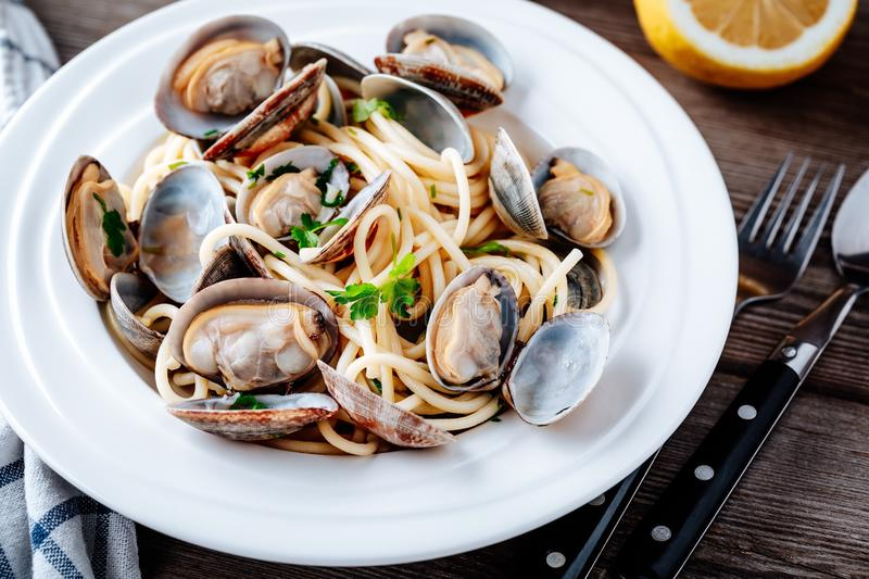 Traditional italian seafood pasta with clams Spaghetti alle Vongole. On wooden background stock photo
