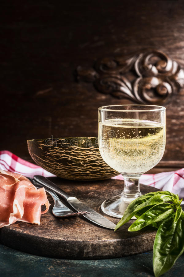 Traditional Italian snack: dry cured ham, melon and glass of wine with cutlery at dark wooden background stock images