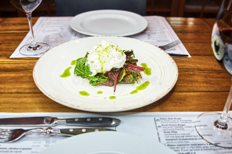 Traditional Italian specialty Burrata Cheese on ceramic plate served with olive oil and green salad over a white rustic. Wooden table. Close up stock images