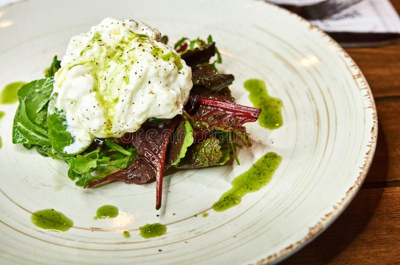 Traditional Italian specialty Burrata Cheese on ceramic plate served with olive oil and green salad over a white rustic. Wooden table. Close up stock photo