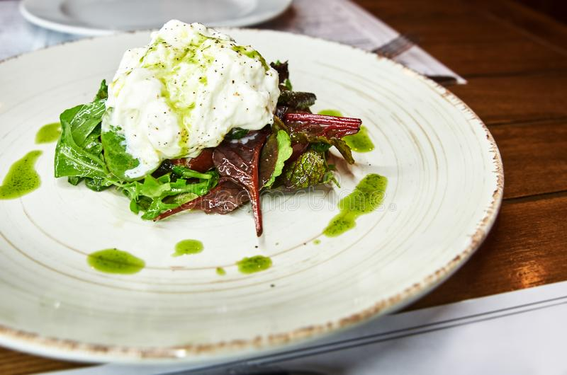 Traditional Italian specialty Burrata Cheese on ceramic plate served with olive oil and green salad over a white rustic. Wooden table. Close up royalty free stock photography