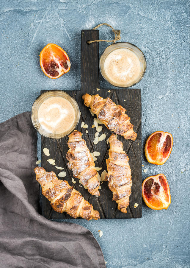 Traditional Italian style home breakfast. Latte in glasses, almond croissants and red bloody Sicilian oranges over. Italian style home breakfast. Latte coffee royalty free stock photo