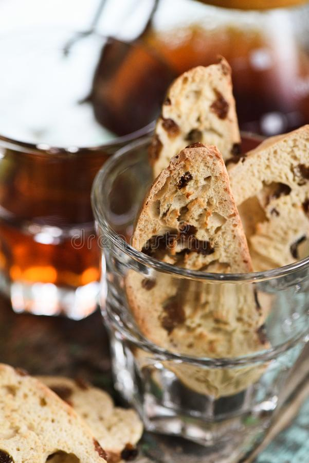 Traditional Italian sweet pastry biscotti or cantucci with raisins in glass served with drip coffee. Closeup stock photo