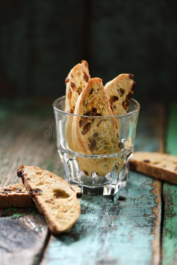 Traditional Italian sweets biscotti or cantucci in glass on old shabby wooden background side view. Copyspace royalty free stock photography