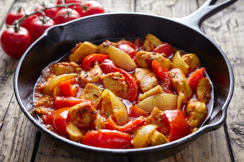 Traditional jalfrezi chicken Indian spicy meat and vegetables dish in cast iron pan stock images