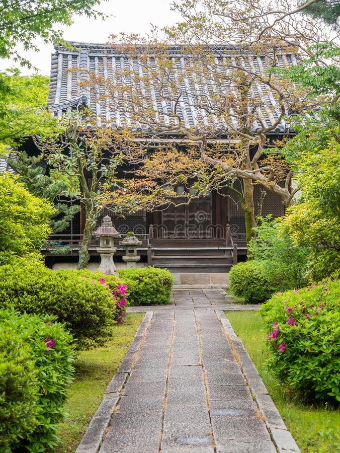 Traditional japan wooden temple with flowers and green trees in front of it stock images