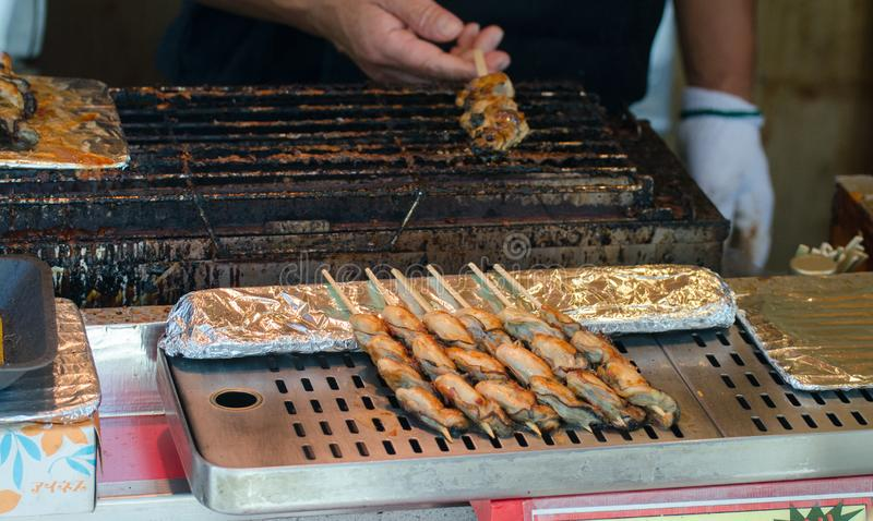 Traditional japanese chicken yakitori - chicken meat grilled served on skewers, at street food market stock photography