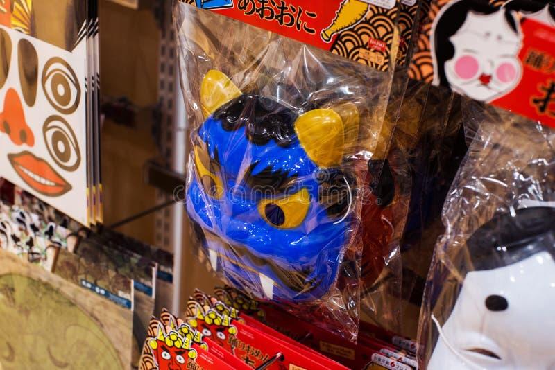 Traditional japanese folk art culture mask of evil oni. Interior of Daiso 100 yen shop stock photos