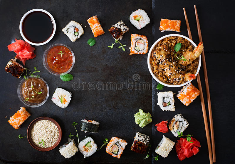 Traditional Japanese food - sushi, rolls, rice with shrimp and sauce on a dark background. royalty free stock photo