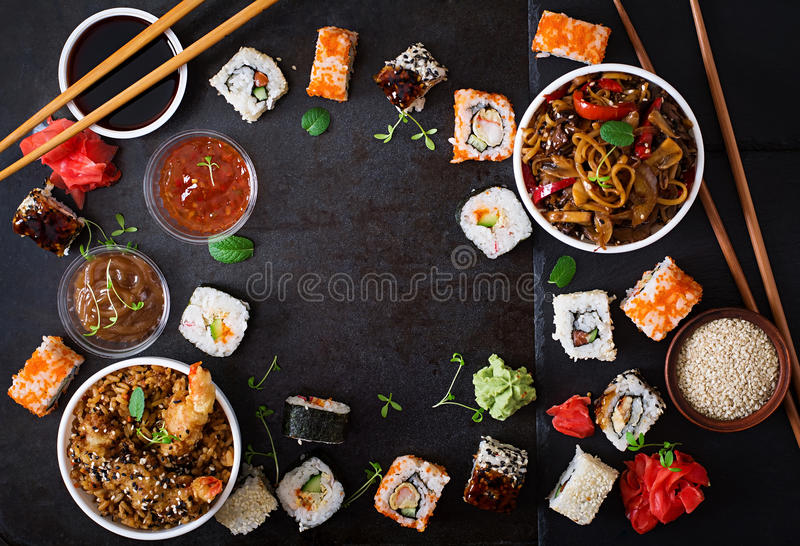 Traditional Japanese food - sushi, rolls, rice with shrimp and udon noodles with chicken and mushrooms on a dark background. stock photography