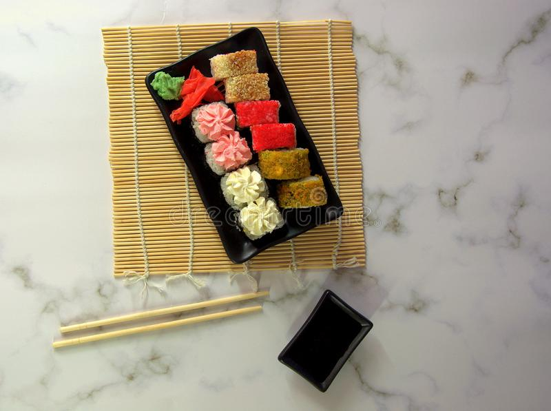 Traditional Japanese food sushi, a set of rolls on a plate with wasabi and seasoning, next to chopsticks and a bowl of soy sauce stock photos