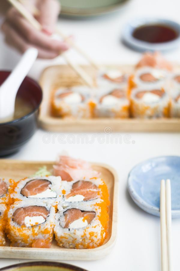 Traditional japanese salmon roll set on wooden plate in restaurant. Hand with chopsticks in background. POV. Lunch, Dinner concept royalty free stock image