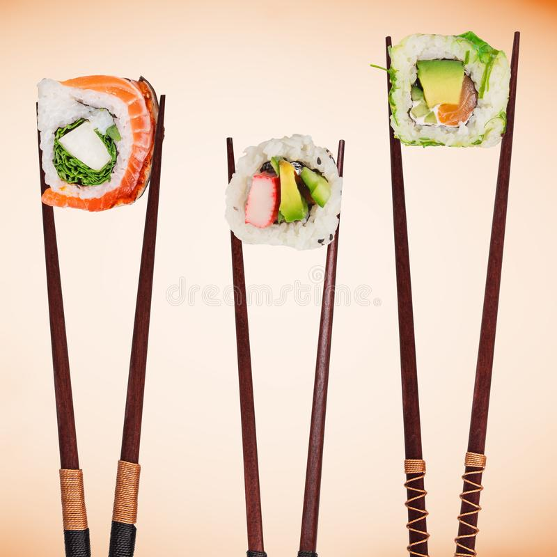 Traditional japanese sushi pieces placed between chopsticks, separated on pastel background. royalty free stock image