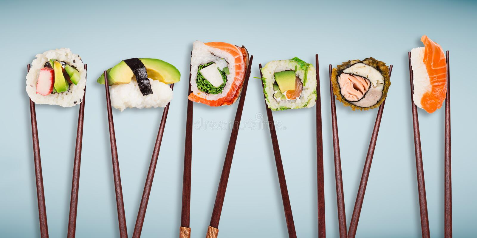 Traditional japanese sushi pieces placed between chopsticks, separated on pastel background. stock image