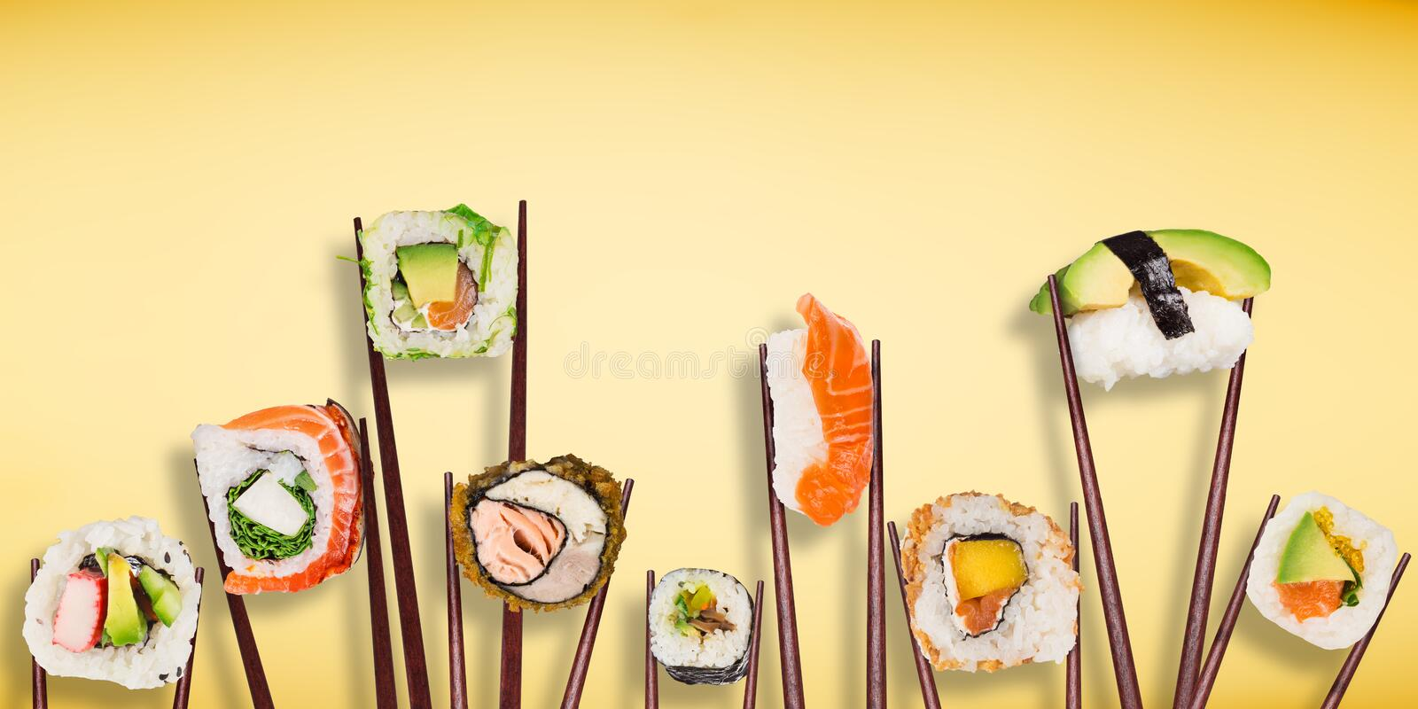 Traditional japanese sushi pieces placed between chopsticks, separated on pastel background. stock photos