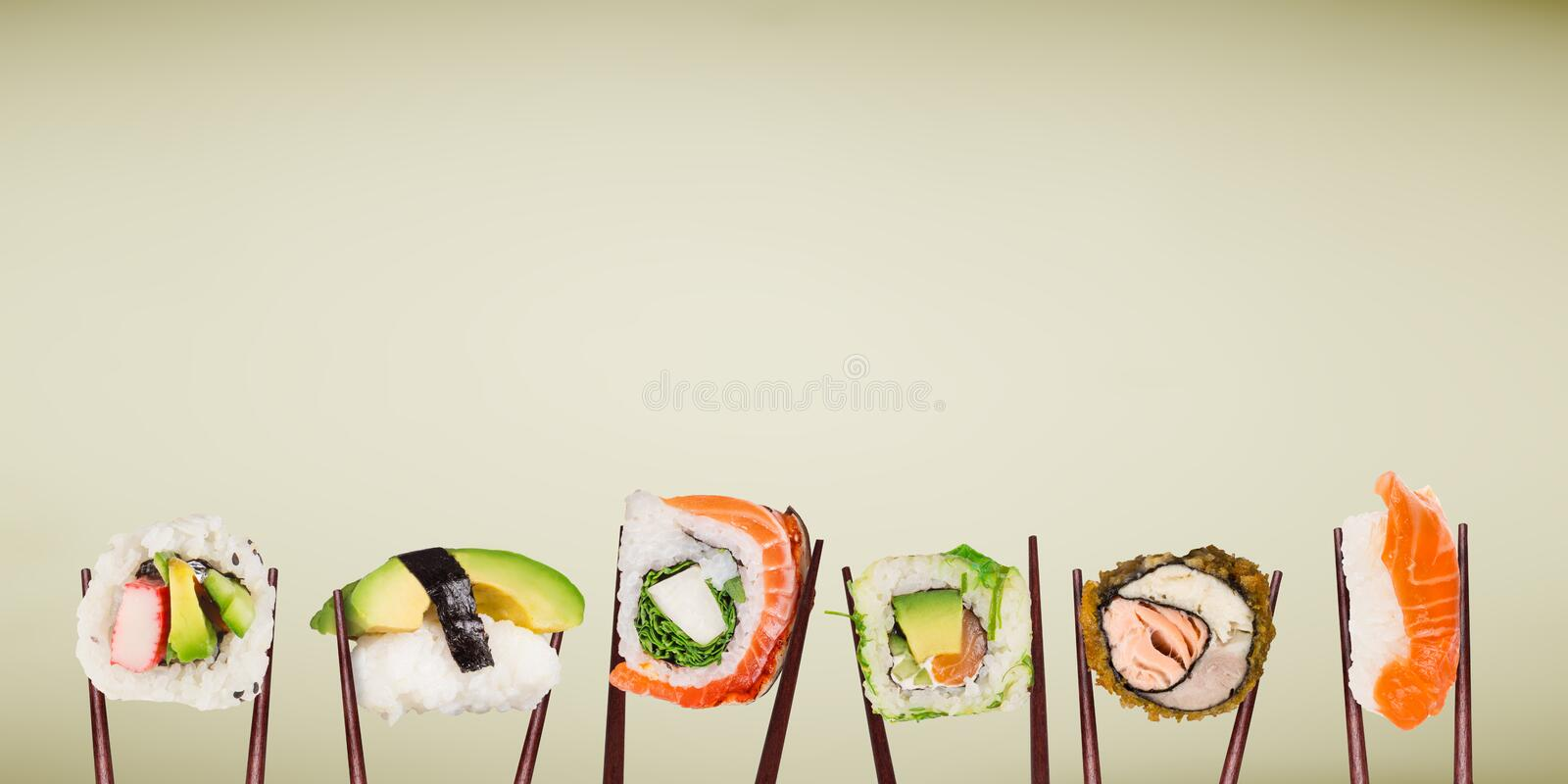 Traditional japanese sushi pieces placed between chopsticks. stock photos