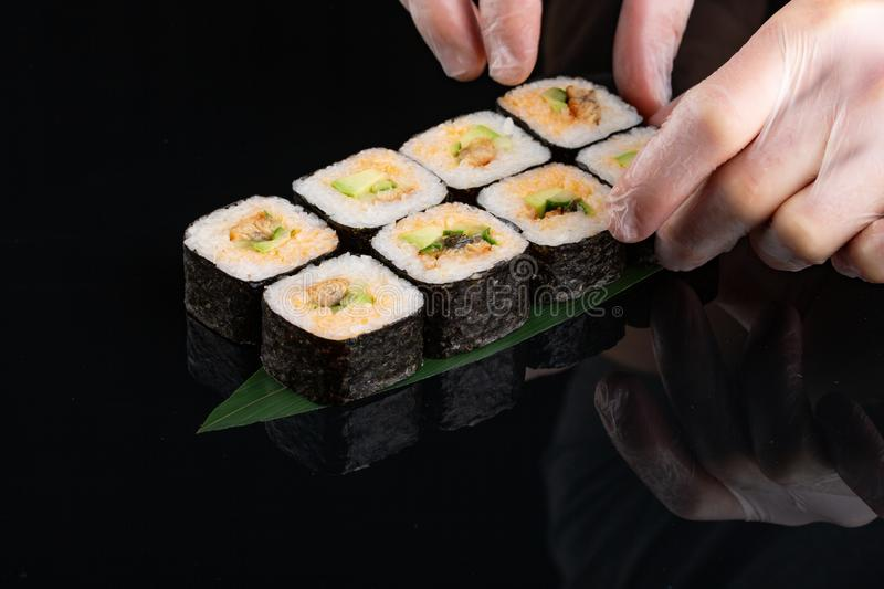 Traditional japanese sushi roll with sea eel, and avocado on a glossy black background stock photo