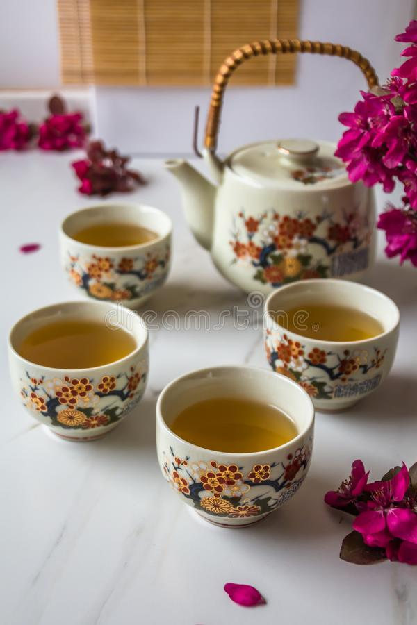 Traditional Japanese tea set filled with green tea and fresh red cheery blossom against white marble back stock photography