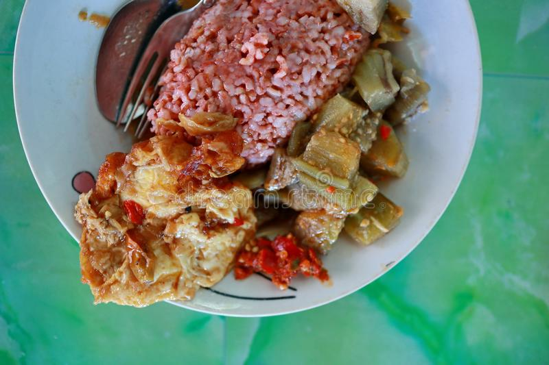 Traditional Javanese food containing red rice with eggplant and egg dishe. S, cooked in spicy Javanese cuisine plus sambel uleg from red chili stock image