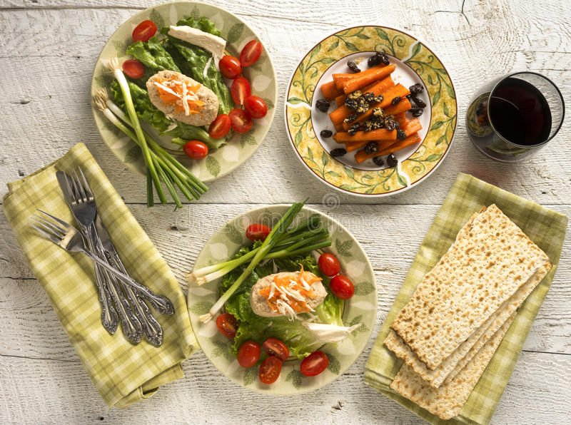 Traditional Jewish Passover dishes of Gefilte Fish and Tsimmes. With red wine and matzah on white wood stock images