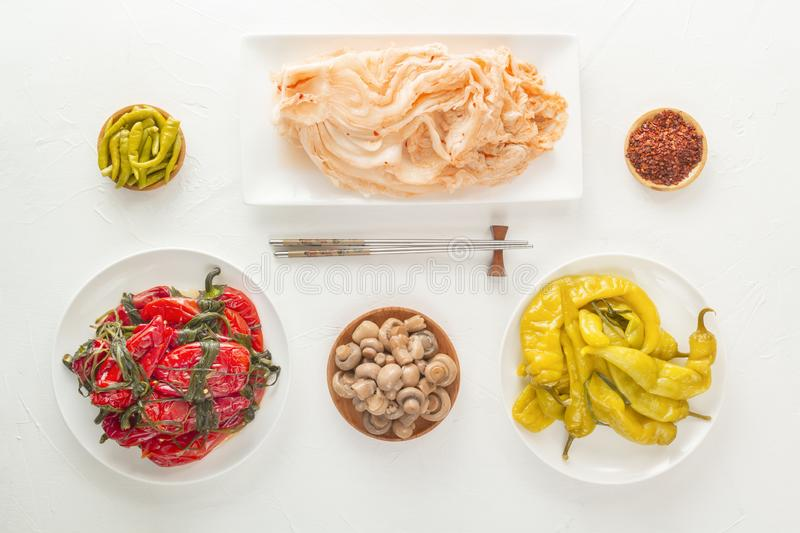 Traditional Korean fermented food - red hot peppers with greens, yellow salted peppers and kimchi cabbage on a white table. Top view royalty free stock images