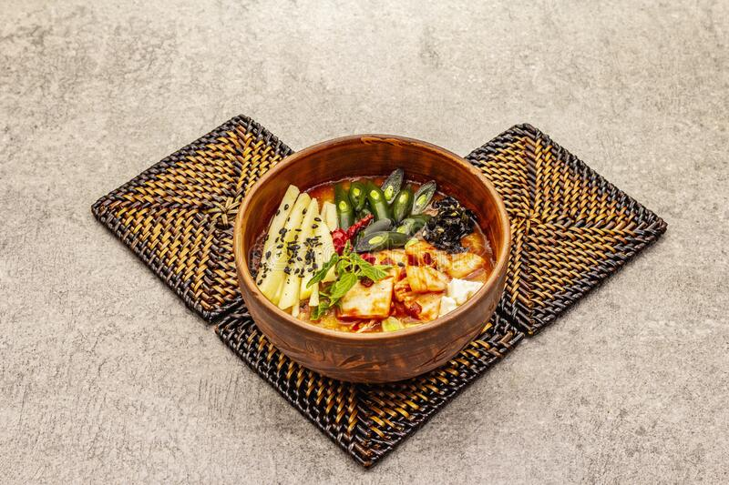 Traditional Korean spicy soup with kimchi, tofu, vegetables. Hot dish for healthy meal. Stone concrete background, copy space stock photography
