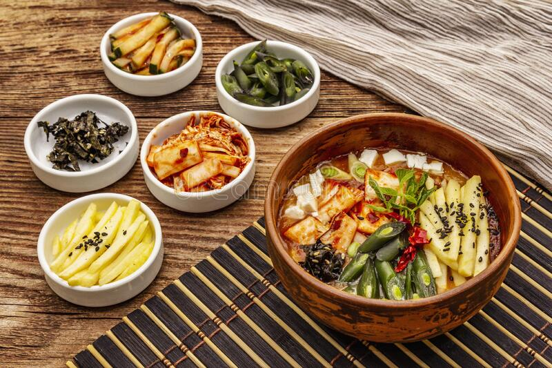 Traditional Korean spicy soup with kimchi, tofu, vegetables. Hot dish for healthy meal. Wooden table background, copy space royalty free stock images