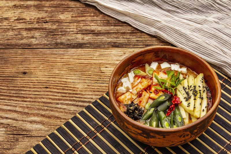 Traditional Korean spicy soup with kimchi, tofu, vegetables. Hot dish for healthy meal. Wooden table background, copy space stock images