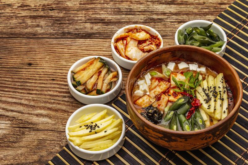 Traditional Korean spicy soup with kimchi, tofu, vegetables. Hot dish for healthy meal. Wooden table background, copy space stock photography