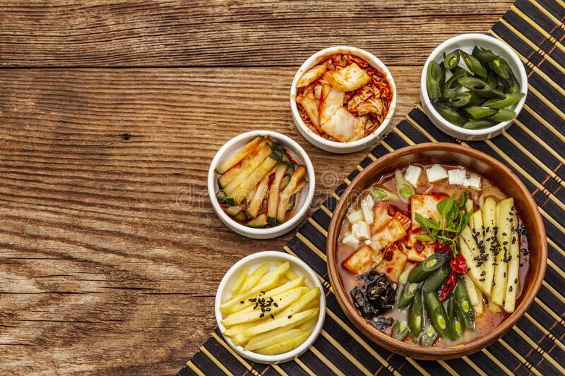 Traditional Korean spicy soup with kimchi, tofu, vegetables. Hot dish for healthy meal. Wooden table background, top view stock photo