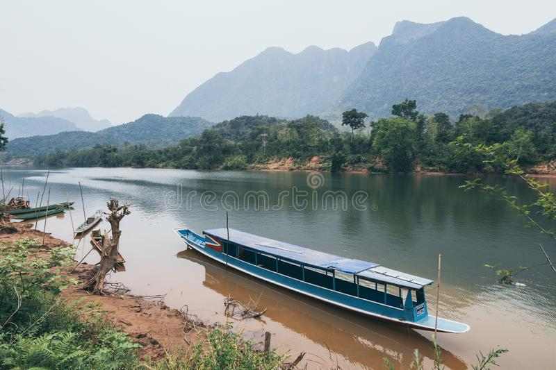 Traditional Laotian wooden slow boat on Nam Ou river near Nong Khiaw village, Laos. Reflection in water, slowboat, vehicle, transportation, authentic royalty free stock images