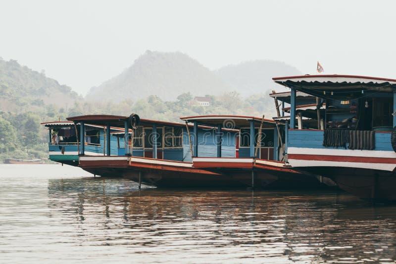 Traditional Laotian wooden slow boats on Mekong river near Luang Prabang, Laos. Traditional Laotian wooden slow boats on Mekong river near Luang Prabang at royalty free stock photography