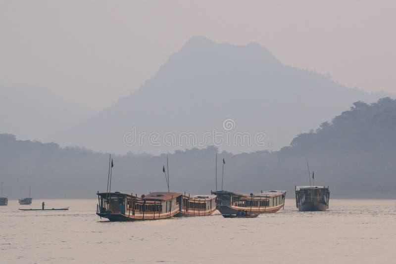Traditional Laotian wooden slow boats on Mekong river near Luang Prabang, Laos. Traditional Laotian wooden slow boats on Mekong river near Luang Prabang at royalty free stock image