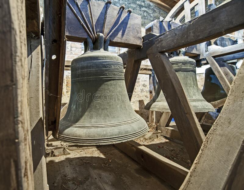 Large old bells in a church tower. Traditional large old bells hanging in an english church tower from the middle ages stock photos