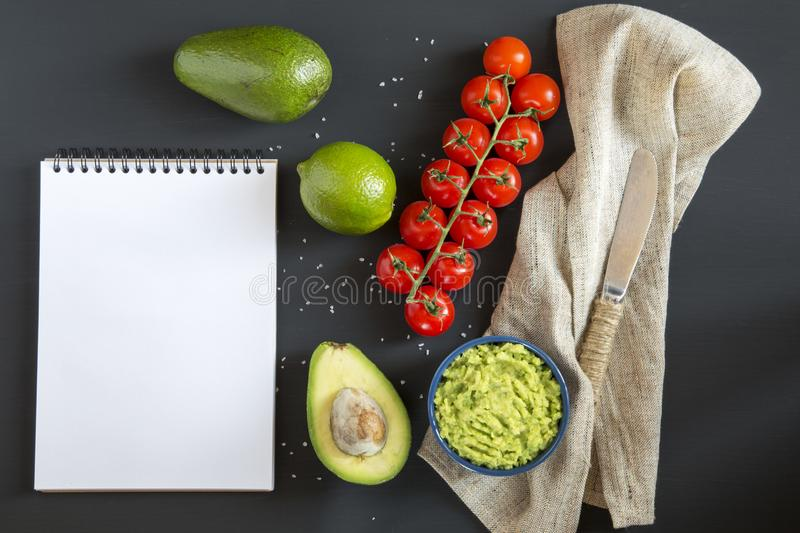 Traditional latinamerican mexican sauce guacamole in ceramic bowl and ingredients on dark background. Notebook. Copy space. Top view. Flat lay royalty free stock images