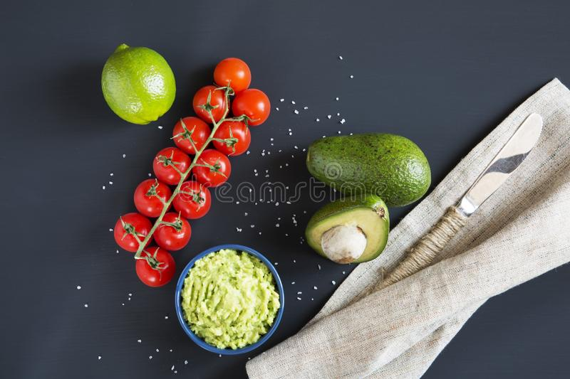 Traditional latinamerican mexican sauce guacamole in ceramic bowl and ingredients on dark background. Top view. Flat lay stock photo