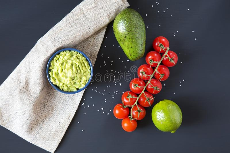 Traditional latinamerican mexican sauce guacamole in ceramic bowl and ingredients on dark background. Top view. Flat lay royalty free stock photo