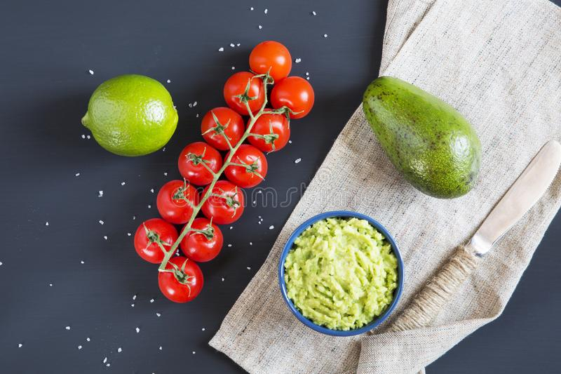 Traditional latinamerican mexican sauce guacamole in ceramic bowl and ingredients on dark background. Top view. Flat lay stock images