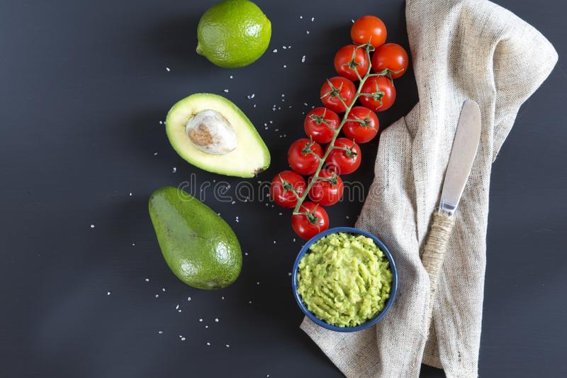 Traditional latinamerican mexican sauce guacamole in ceramic bowl and ingredients on dark background. Top view. Flat lay stock photography